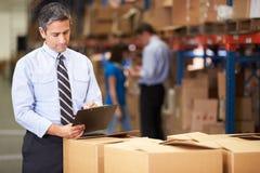 Менеджер в коробках склада проверяя Стоковое Изображение RF