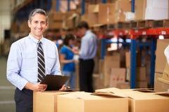 Менеджер в коробках склада проверяя Стоковые Фото