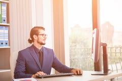 Менеджер в костюме работая на его компьютере рядом с стеклянным окном Стоковое Изображение