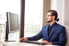 Менеджер в костюме работая на его компьютере рядом с стеклянным окном Стоковая Фотография
