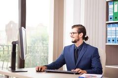 Менеджер в костюме работая на его компьютере рядом с стеклянным окном Стоковая Фотография RF