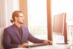 Менеджер в костюме работая на его компьютере рядом с стеклянным окном Стоковые Фотографии RF