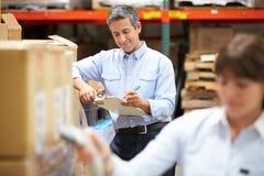 Менеджер в складе с коробкой скеннирования работника в переднем плане Стоковое фото RF