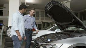Менеджер демонстрирует клиента мотор в современном автомобиле акции видеоматериалы
