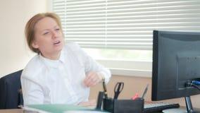 Менеджер женщины утомлял работы делая физические упражнения на таблице в офисе видеоматериал
