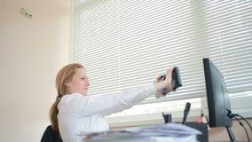 Менеджер женщины утомлял работы делая физические упражнения на таблице в офисе сток-видео