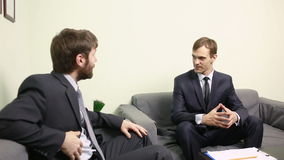 Менеджер интервьюируя мужского заявителя в его офисе костюмы 2 бизнесменов сток-видео