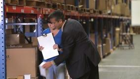 Менеджер и работник проверяя товары в складе сток-видео