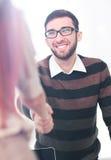 Менеджер приветствуя нового работника и усмехаясь в офисе Стоковое фото RF