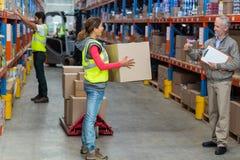 Менеджер смотря работника держа картонные коробки с большими пальцами руки вверх Стоковая Фотография