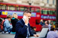 Менеджер с компьтер-книжкой и телефоном против двухэтажного автобуса красного цвета Londons Стоковая Фотография