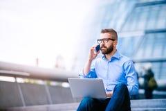 Менеджер с компьтер-книжкой и умным телефоном, здание муниципалитетом Лондона Стоковое Фото