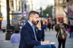 Менеджер с компьтер-книжкой и умным телефоном, солнечным цирком Piccadilly, Lo Стоковое Фото