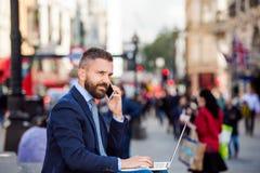 Менеджер с компьтер-книжкой и умным телефоном, солнечным цирком Piccadilly, Lo Стоковые Изображения