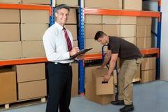 Менеджер с доской сзажимом для бумаги и работником в складе Стоковое Изображение RF