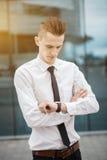 Менеджер умного бизнесмена смотря вахту, наблюдает время владение домашнего ключа принципиальной схемы дела золотистое достигая н Стоковые Изображения