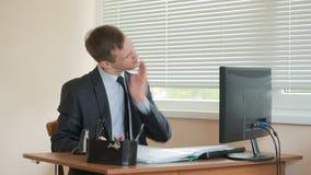 Менеджер утомлял работы делая физические упражнения на таблице в офисе сток-видео