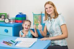 Ментор и пятилетняя девушка joyfully показывают большие пальцы руки вверх путем делать регулярн работу Стоковые Фото