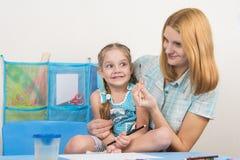 Ментор и пятилетняя старая девушка имея потеху смотря, что щетку нарисовать Стоковая Фотография RF