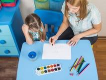 Ментор и пятилетняя старая девушка на таблице рисуют изображение в детском саде Стоковая Фотография RF