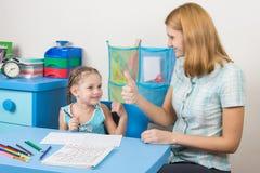 Ментор счастливо показывает пятилетние большие пальцы руки девушки вверх, поздравляющ ее Стоковое фото RF