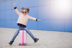 Меньшая девушка моды курчавая усмехаясь в солнечных очках распологая на чемодан и показывая мир пальцами Перемещение концепции Стоковое Изображение