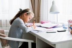 Меньшая девушка школы делая домашнюю работу Стоковая Фотография