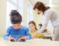 Меньшая девушка школы с ПК таблетки над классом Стоковая Фотография RF