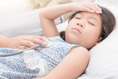 Меньшая девушка экзаменов доктора руки больная с стетоскопом Стоковая Фотография RF