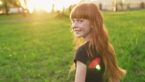 Меньшая красивая девушка redhead идет встретить солнце и смотрит в камеру сток-видео