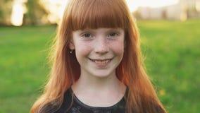 Меньшая красивая девушка redhead с веснушками усмехаясь и смотря камеру сток-видео