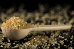 Меньшая ложка woode заполнила с желтым сахарным песком на темном шифере Стоковые Изображения