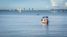 Меньшая рыбацкая лодка на воде на пляже с голубым небом и городом на заднем плане Стоковая Фотография RF