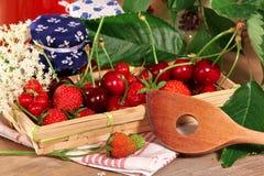 Меньшее варенье раздражает с вишнями и деревянной ложкой Стоковое Изображение