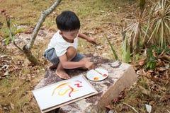 Меньшее играя panit на белой бумаге в саде Стоковое Изображение