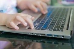Меньшее касание руки на тетради клавиатуры Стоковые Фотографии RF