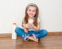 Меньшее питье девушки smiley молоко в ее доме Стоковое Фото