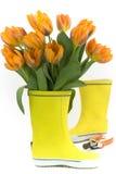 Меньшие ботинки дождя и свежие тюльпаны Стоковые Изображения