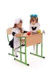 Меньшие девушки школы сидя на столе и читая книгу Стоковая Фотография