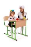 Меньшие девушки школы сидя на столе и читая книгу Стоковое Изображение