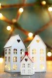 Меньшие дома рождества игрушки с горящей внутренностью света на blured зеленой предпосылке Стоковое фото RF
