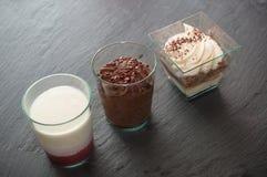 Меньшие стеклянные десерты на предпосылке доски Стоковое Изображение RF
