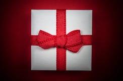 Меньший белый подарок изолированный на красной предпосылке стоковое изображение rf