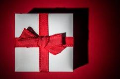 Меньший белый подарок изолированный на красной предпосылке стоковые фотографии rf