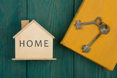 меньший дом с текстом & x22; Home& x22; , книга и ключи стоковое фото