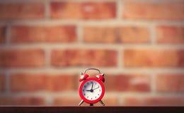 Меньший красный будильник на таблице Стоковые Фото