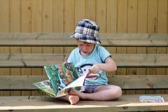 Меньший мальчик redhead читает книгу Стоковое Изображение RF
