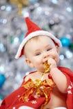 Меньший младенец рождества в костюме Санты Ребенок держа голубой шарик около праздника освещает предпосылку Стоковые Изображения