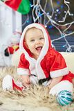 Меньший младенец рождества в костюме Санты Ребенок держа голубой шарик около праздника освещает предпосылку Стоковые Фото