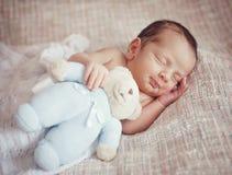Меньший младенец спит сладко с игрушкой в его руках стоковое фото rf